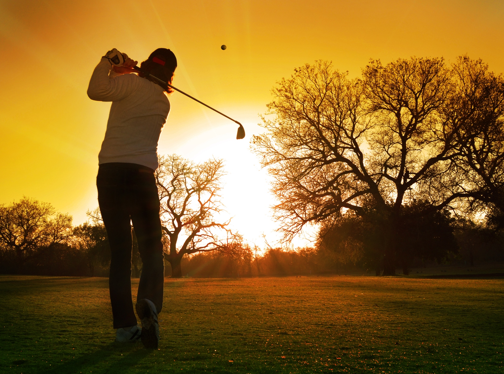 Golfer hitting into the sunset